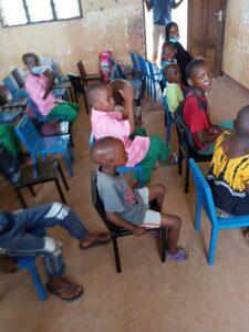 Elever sitter på donerade stolar i klassrum
