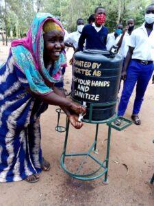 Lärare tvättar händerna i vattentank