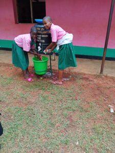 Elevertvättar händerna i vattentank
